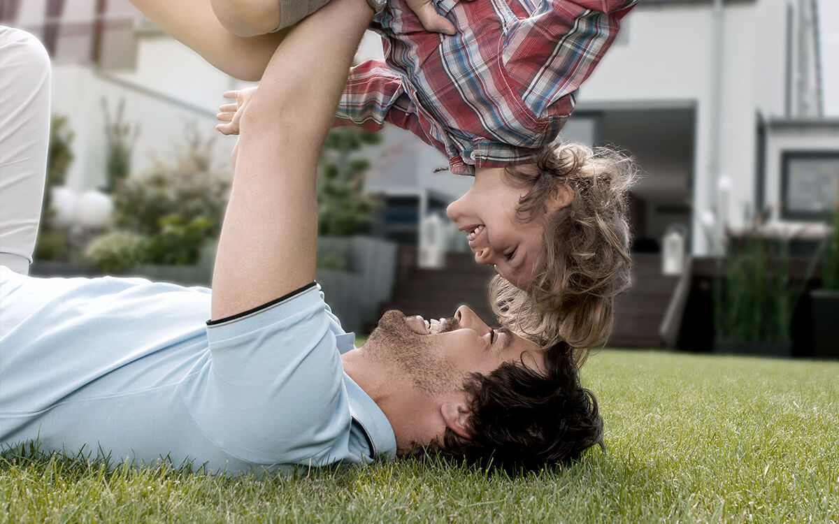 Vater spielt mit Sohn im Garten, Immobilie im Hintergrund